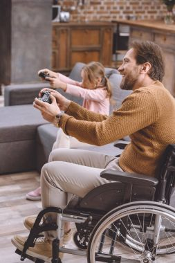 happy daughter and father on wheelchair playing video game with joysticks