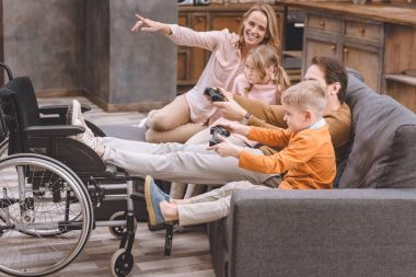 happy family with disabled father putting legs on wheelchair and playing with joysticks at home