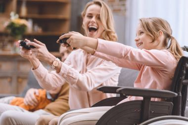 cheerful family with disabled child in wheelchair playing with joysticks together at home
