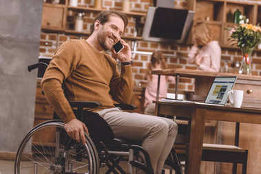 smiling disabled man in wheelchair talking on smartphone and using laptop at home
