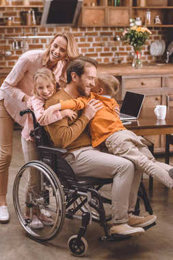 happy family with two kids and father in wheelchair hugging together at home