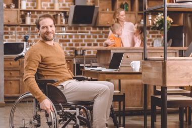 disabled middle aged man in wheelchair smiling at camera while spending time with family at home