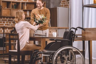 smiling man presenting flowers to disabled wife and wheelchair standing near by