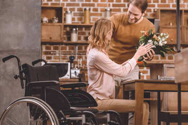 smiling man presenting flowers to disabled wife at home