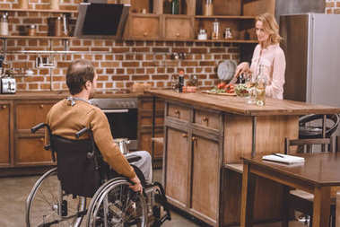 woman with disabled man in wheelchair cooking dinner together at home