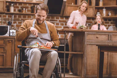 smiling man in wheelchair cutting vegetables for salad while happy mother and daughter standing behind