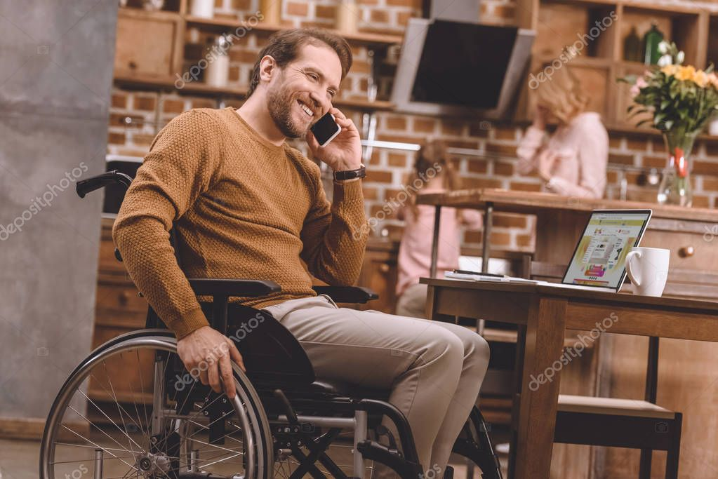 happy disabled man in wheelchair talking on smartphone and using laptop at home