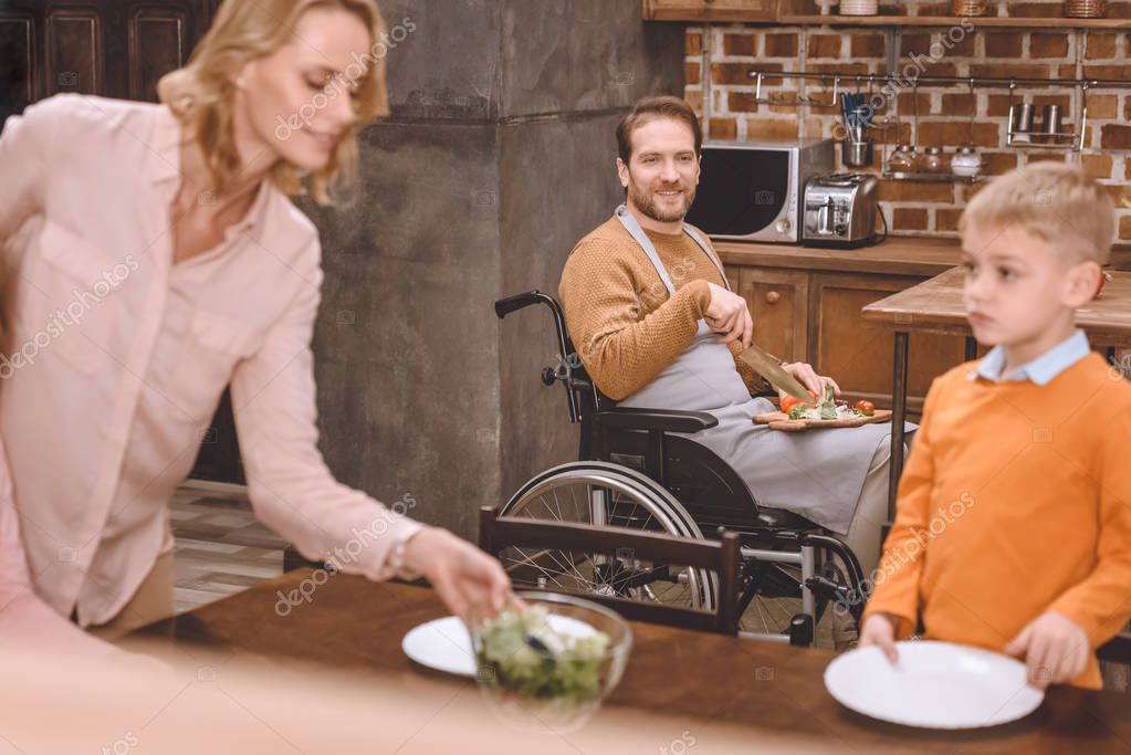 mother with son serving table for dinner while father in wheelchair cutting vegetables at home