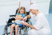 Doktor něco ukazuje na tabletu kid na invalidní vozík