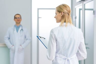 female doctor in white coat with diagnosis in hospital, colleague standing on background
