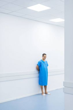 male patient in medical gown standing at wall in hospital