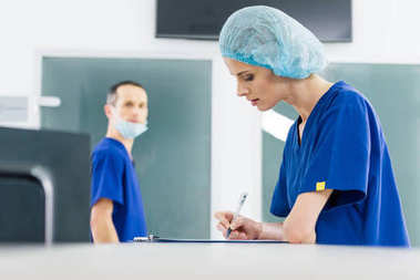 female surgeon writing diagnosis while colleague looking at her in hospital