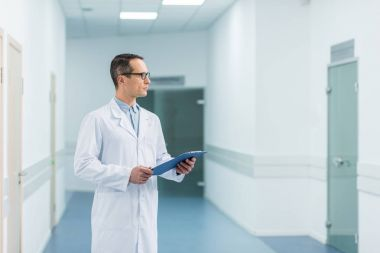 male doctor in white coat holding diagnosis in hospital