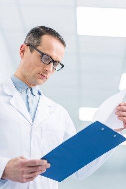 Male doctor in white coat reading diagnosis in hospital stock vector