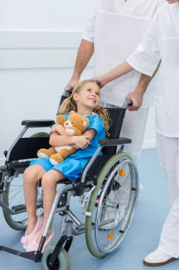 cropped image of doctors moving smiling kid on wheelchair