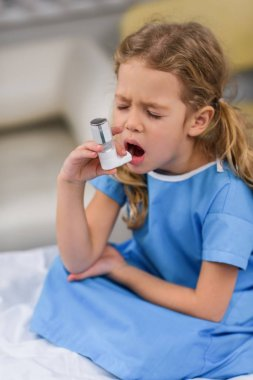 ill kid using asthma inhaler with closed eyes