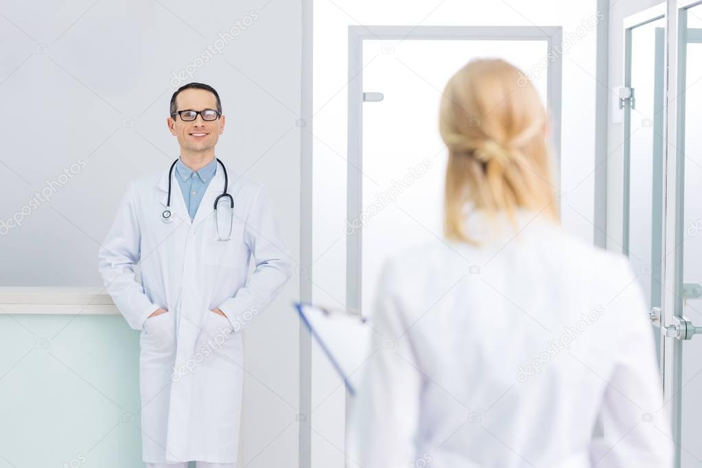 male doctor in white coat with stethoscope looking at his colleague in clinic
