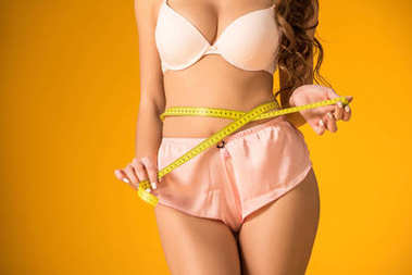 cropped image of sexy girl in lingerie set measuring waist isolated on orange