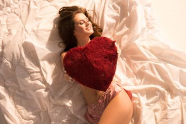top view of smiling girl lying in underwear with heart shaped pillow