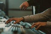 Fotografia ritagliata colpo degli uomini utilizzando equalizzatore grafico analogico a studio di registrazione