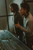 Fotografia sorridente giovani produttori suoni in studio di registrazione