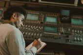 Fotografia bello giovane musicista scrivendo nel notebook presso uno studio di registrazione