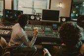 Fotografia vista posteriore di produttori sani guardando monitor vuoto nello studio di registrazione