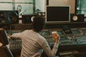 Fotografia produttore audio con tazza monouso di caffè lavorava presso lo studio