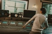 young sound producer recording song at studio