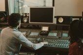 Fotografia produttori sani guardando monitor vuoto nello studio di registrazione