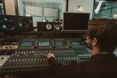 Fotografia bello giovane produttore suono lavorando in studio di registrazione