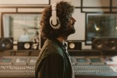 Photo side view of sound producer in headphones enjoying music at studio