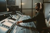 side view of concentrated sound producer working at studio
