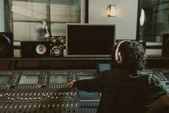 zadní pohled na zvukový producent pracuje ve studiu při nahrávání skladby