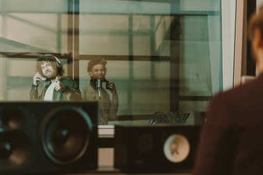 young happy musicians recording song behind glass at studio and showing thumbs up