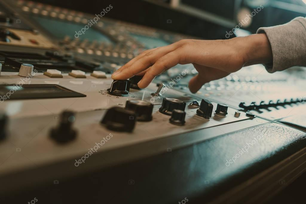 Cropped shot of sound producer touching knobs on recording equipment stock vector