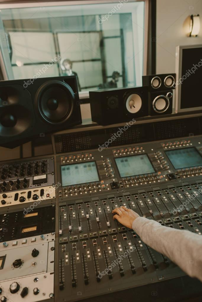 Cropped shot of sound producer working with graphic equalizer at studio stock vector
