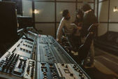 blurred group of musicians spending time at recording studio with graphic equalizer