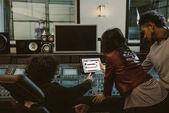 Zvuková výrobci společně pomocí tabletu v nahrávacím studiu s soundcloud webové stránky na obrazovce