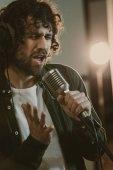 Fotografie emotionaler junge Sänger im Lied im Studio Kopfhörer