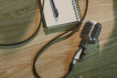 Photo top view of wired vintage microphone lying on wooden table with blank notebook