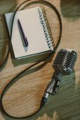 Photo top view of wired retro microphone lying on wooden table with blank notebook