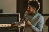 Fotografie gut aussehend afroamerikanische Sängerin Durchführung Song mit Mikrofon