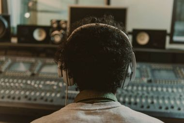 back view of sound producer in headphones sitting at studio