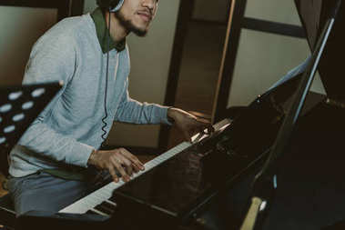 cropped shot of african american man playing piano at studio