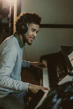 happy young african american man playing piano at studio