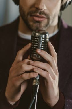 cropped shot of singer holding microphone and performing song