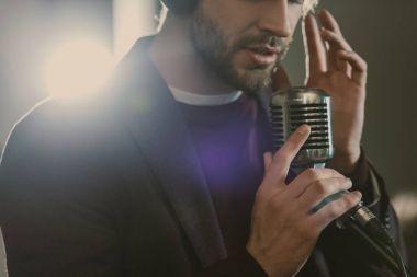 Attractive young singer in headphones performing song at studio stock vector