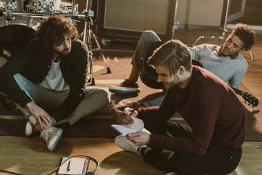 young music band writing lyrics together while sitting on floor