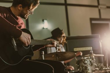 handsome young musician playing guitar on repetition with blurred female drummer behind